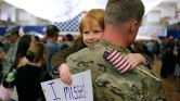 FORT CARSON, CO - NOVEMBER 4: Gavin Shaw, 5, flashes a smile as he hugs his father, Master Sergeant Adam Shaw, during a Welcome Home Ceremony for approximately 230 4th Brigade Combat Team soldiers, November 4, 2012 in Fort Carson, Colorado. The soldiers had been deployed for nine months in various regions of Afghanistan. (Photo by Marc Piscotty/Getty Images)