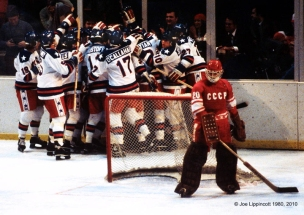 As USSR backup Goalie Vladislav Tretjak (20) contemplates his team's loss, Team USA celebrate their 4-3 upset defeat of the Soviets at the XIII Winter Olympics on February 22, 1980, at Lake Placid, N.Y.