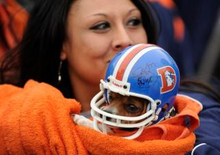 Corina Maestas holds her dog, named Bronco Boy, Friday, January 13, 2012, during a Denver Broncos Spirit Rally on Bannock Street in front of the Denver City and County Building. Fans covered the street with chalk art messages for the team. RJ Sangosti, The Denver Post