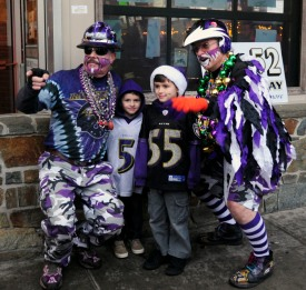 "Fans ""Ravin Rick"" Dixon, left, and Matt ""Fan Man"" Andrews, right, pose for a quick photo with young fans Ryan and Dominic Bonitz during Friday night's Ravens Rally at Looney's in Bel Air."