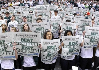 Jan 25, 2014; East Lansing, MI, USA; Michigan State Spartans Izzone read newspapers prior to a game against the Michigan Wolverines at Jack Breslin Student Events Center. Mandatory Credit: Mike Carter-USA TODAY Sports ORG XMIT: USATSI-150168 ORIG FILE ID: 20140125_ajl_bc2_238.JPG
